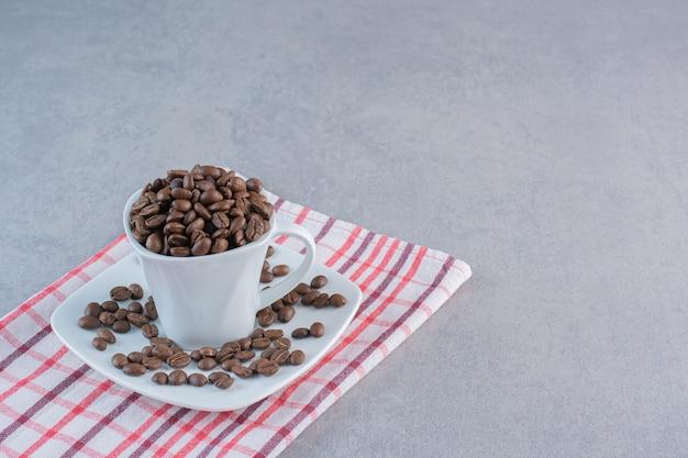 Una tazza bianca di chicchi di caffè tostati sulla tovaglia a righe.