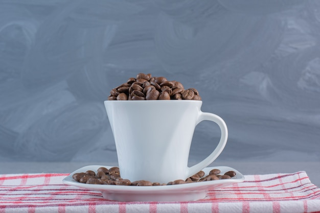 A white cup of roasted coffee beans on striped tablecloth.