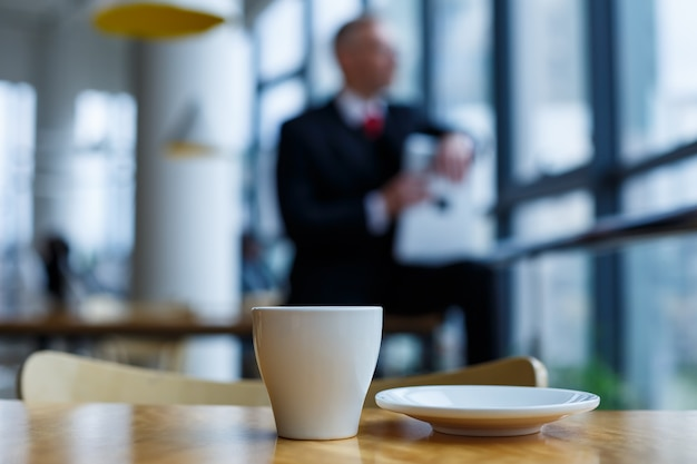 A white cup and saucer with hot aromatic coffee stands on a wooden table against the background of a sitting businessman
