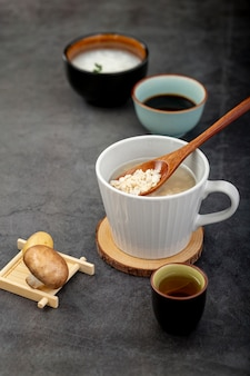 White cup of soup on a wooden support with a mushroom