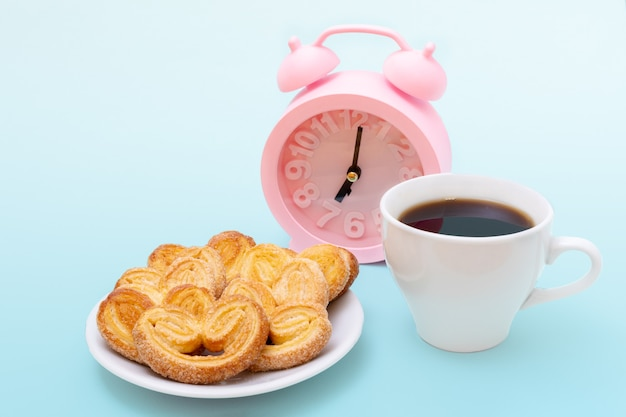 White cup of steaming hot black coffee or hot chocolate, freshly baked heart shaped cookies and pink alarm clock on light blue background,
