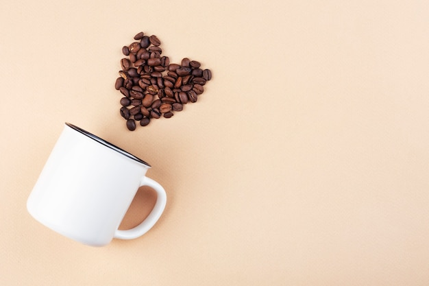 White cup on the table, top view, coffee beans in the shape of a heart
