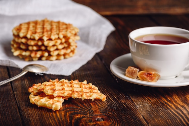 White cup of tea with belgian waffles stack on napkin and pieces of waffle on wooden surface.