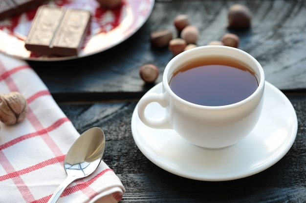 A white cup of tea with chocolate bar and nuts around.