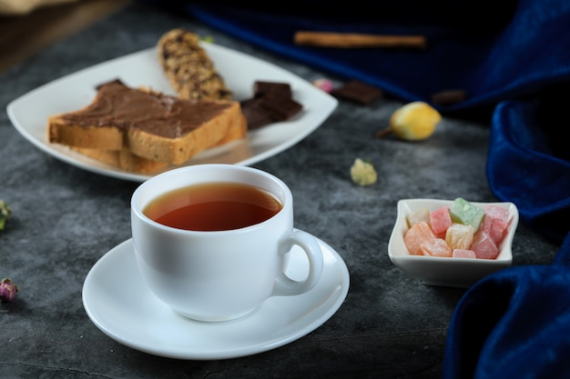 A white cup of tea with chocolate toast bread