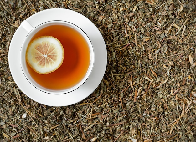 White cup of tea with lemon on dry herbs.