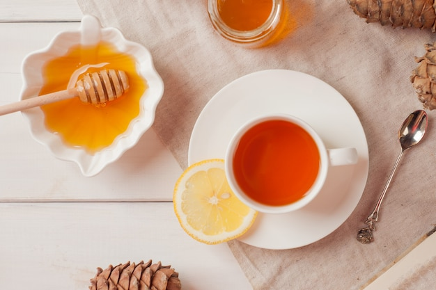 White cup of tea with lemon, honey on wooden table background.
