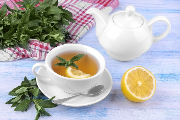 White cup of tea with mint and lemon and a kettle on a blue wooden background