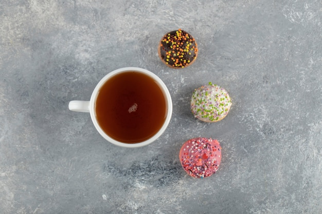 A white cup of tea with small delicious doughnuts .