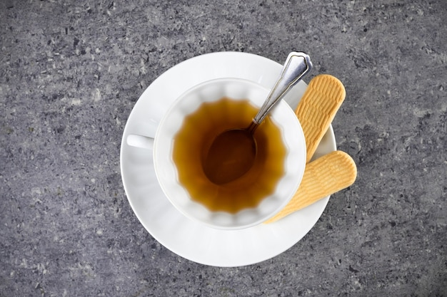 White cup of tea with spoon and saucer with two cookies. on granite surface, top view.