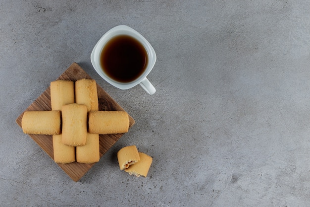 A white cup of tea with sweet fresh cookies in a wooden board on a stone table.