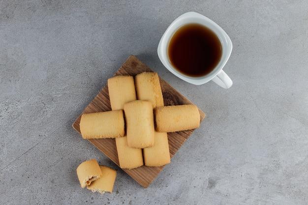 Una tazza di tè bianco con biscotti freschi dolci in una tavola di legno su una pietra.