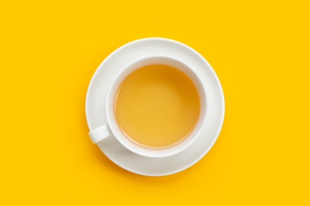 White cup of tea on yellow background