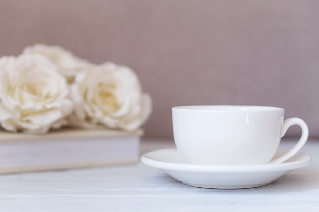 - white cup on white wooden background with roses. wedding, romantic.