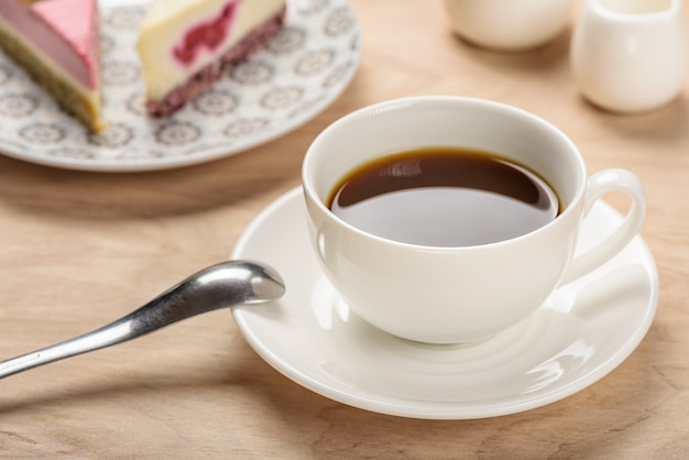 조각 케이크의 배경에 나무 테이블에 접시에 음료와 함께 흰색 컵.