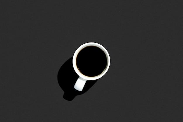 孤立した黒い空間にコーヒーを飲みながら白いカップ。トップビュー、フラットレイアウト