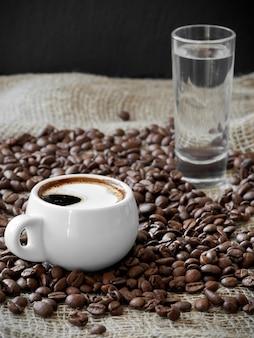 Белая чашка с ароматным кофе эспрессо среди кофейных зерен на мешковине