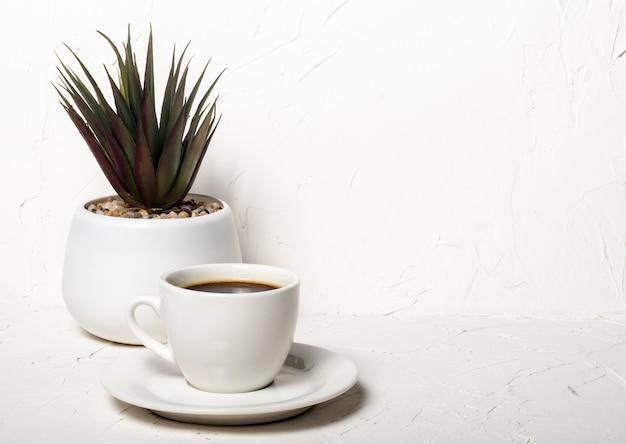 Белая чашка с черным ароматным кофе на белом абстрактном фоне с цветком в горшке на заднем плане с копией пространства.