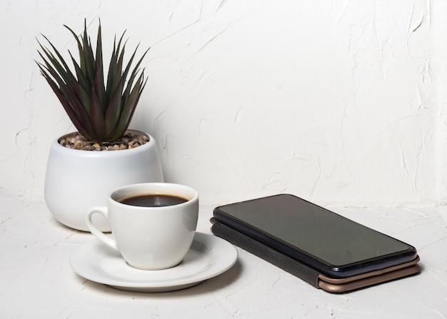 Белая чашка с черным ароматным кофе на белом абстрактном фоне с цветком в горшке на заднем плане со смартфоном.
