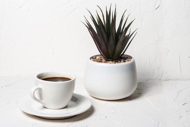 Белая чашка с черным ароматным кофе на белом абстрактном фоне с цветком в горшке на заднем плане.