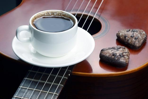 Белая чашка с черным кофе и печеньем, лежащая на акустической гитаре. хобби и развлечения