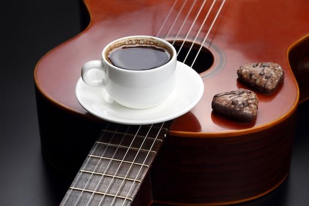 アコースティックギターの上に横たわっているブラックコーヒーとクッキーと白いカップ