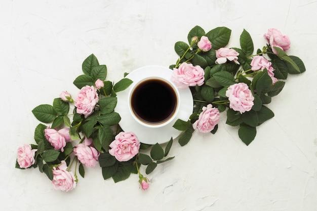 軽い石の表面にブラックコーヒーとピンクのバラと白いカップ。フラット横たわっていた、トップビュー