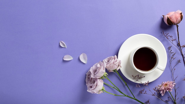 White cup with black coffee and delicate lilac roses, dried flower branches on a lilac background. creative breakfast. flat lay style, banner, copy space