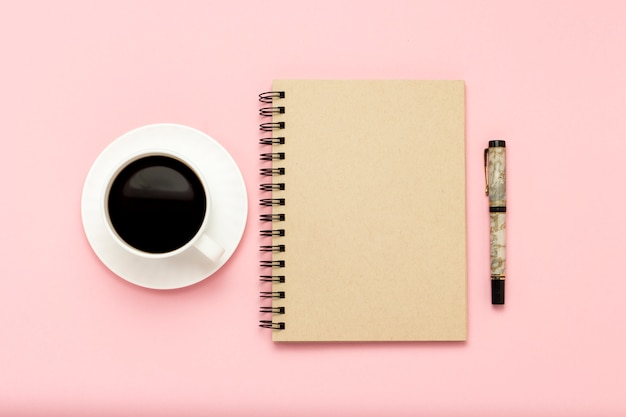 White cup with black coffee, notebook, pen on a pink background. flat lay, top view Premium Photo