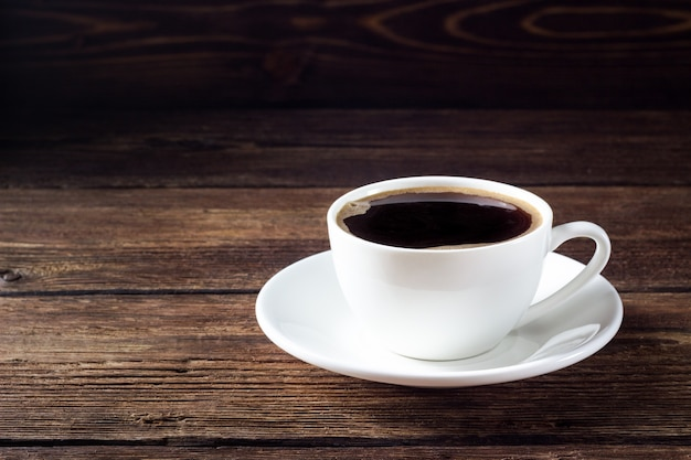 Белая чашка с черным кофе на деревянном столе