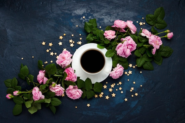 White cup with black coffee, stars and pink roses on a dark blue surface. concept of coffee with flowers and the night sky. flat lay, top view