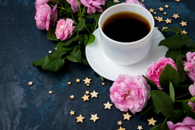 White cup with black coffee, stars and pink roses on a dark blue surface