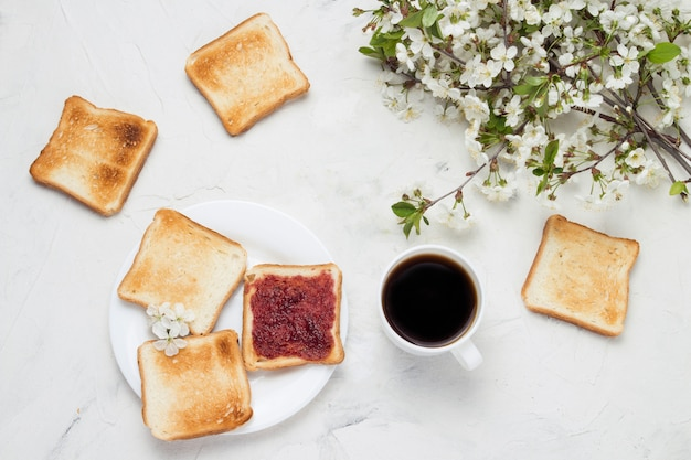 Белая чашка с черного кофе, тосты, джем и весенние цветы на светлом фоне камня. концепция здорового завтрака. плоская планировка, вид сверху