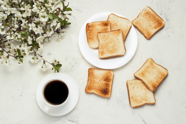 ブラックコーヒー、トースト、ジェム、明るい石の背景に春の花と白いカップ。健康的な朝食のコンセプト。フラット横たわっていた、トップビュー