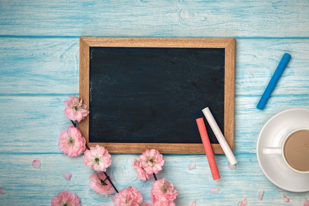 White cup with cappuccino, sakura flowers and chalk board on a blue wooden table.