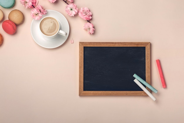 White cup with cappuccino, sakura flowers, chalk board and macarons on pink