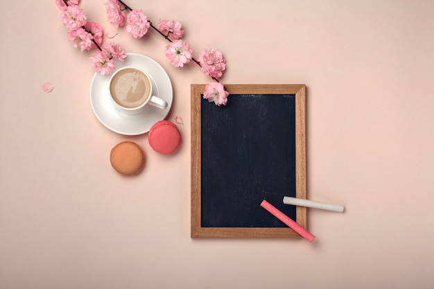 White cup with cappuccino, sakura flowers, chalk board and macarons