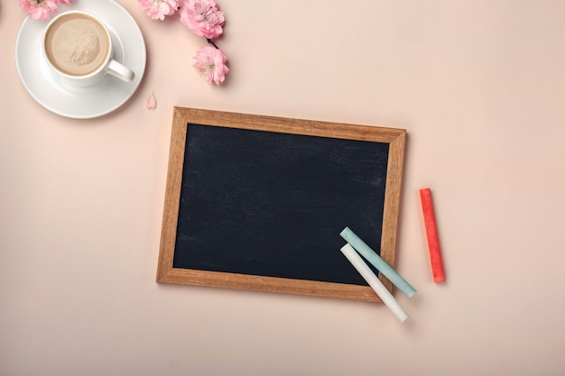 White cup with cappuccino, sakura flowers, chalk board