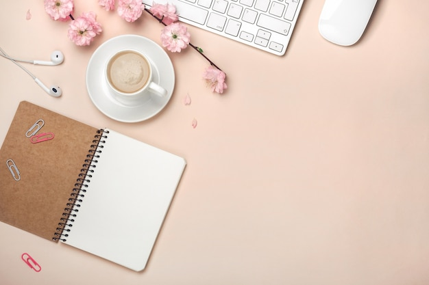 White cup with cappuccino, sakura flowers, keyboard, alarm clock, notebook on a pastel pink background
