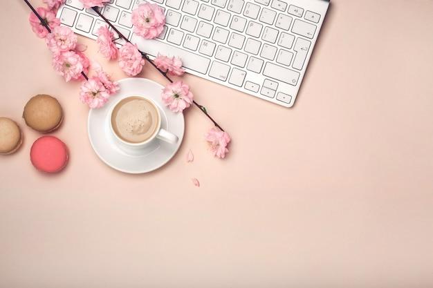 White cup with cappuccino, sakura flowers, keyboard, macarons
