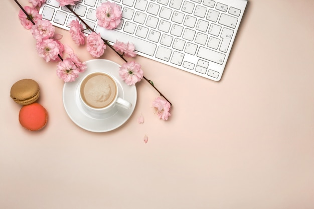 White cup with cappuccino, sakura flowers, keyboard on a pastel pink background