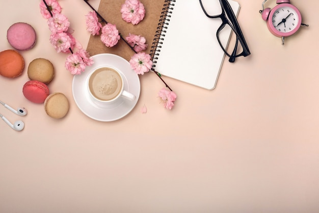 White cup with cappuccino, sakura flowers, macarons, alarm clock, notebook