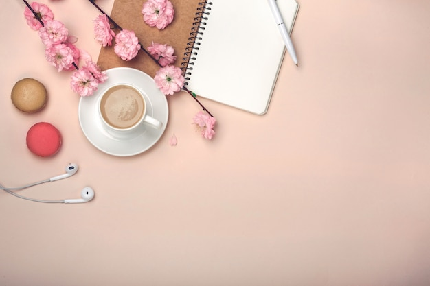 White cup with cappuccino, sakura flowers, macarons, notebook on pink