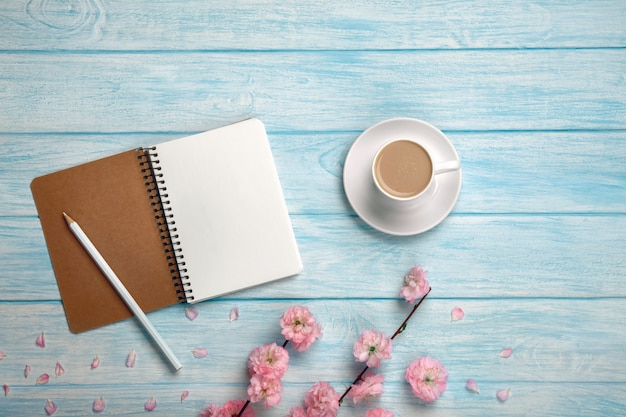 White cup with cappuccino, sakura flowers and notebook on a blue wooden table.