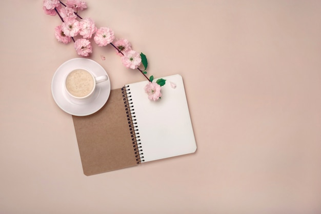 White cup with cappuccino, sakura flowers, notebook on pink