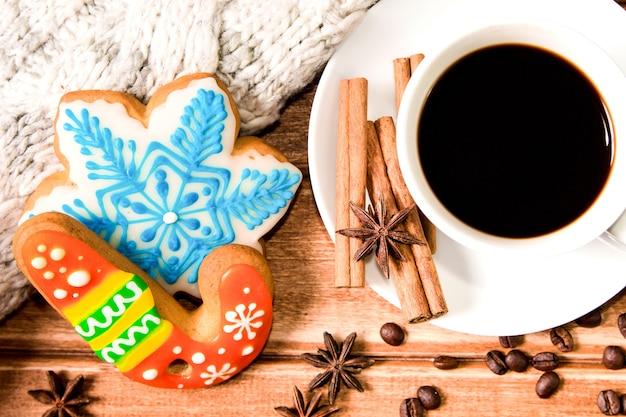Белая чашка с кофе и рождественскими пряниками на деревянном столе