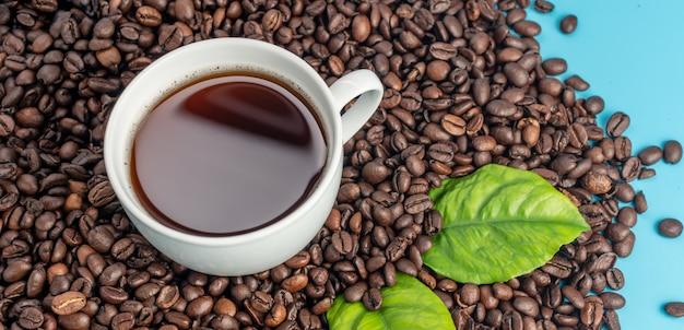 Белая чашка с кофе и кофейными зернами