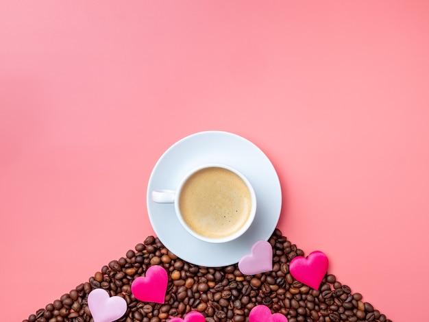 ピンクの背景のコーヒー豆にコーヒーとシルクのハートと白いカップ