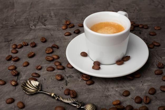 Белая чашка с кофе и цельным зерном темный фон