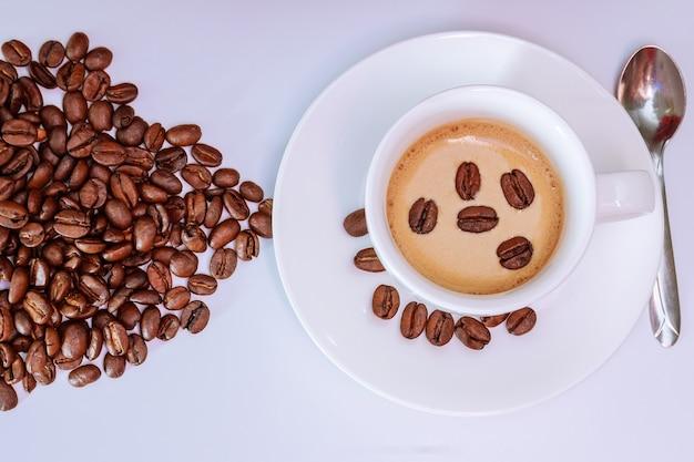 커피와 전체 곡물을 넣은 흰색 컵. 위에서 볼 수 있습니다. 흰 바탕